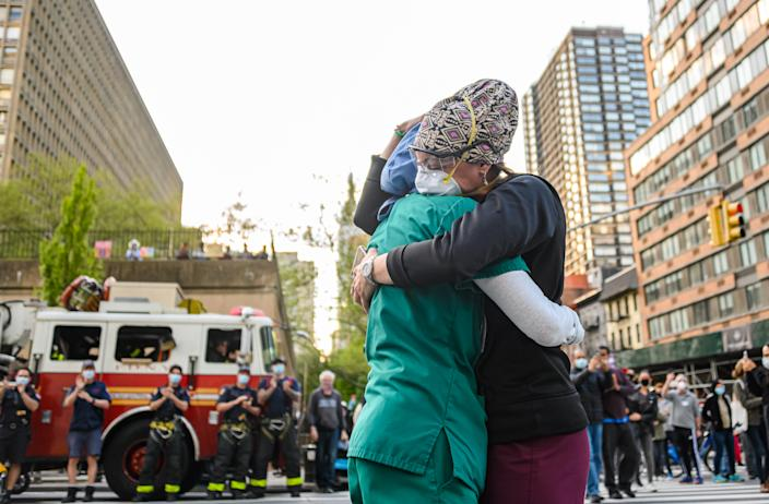 Medical workers hug outside NYU Langone Health hospital as people applaud to show their gratitude for them during the coronavirus pandemic, May 7, 2020. (Photo by Noam Galai/Getty Images)