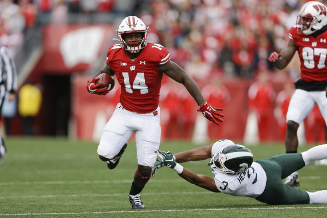 Wisconsin running back Nakia Watson (14) runs past Michigan State safety Xavier Henderson (3) during the first half of an NCAA college football game Saturday, Oct. 12, 2019, in Madison, Wis. (AP Photo/Andy Manis)