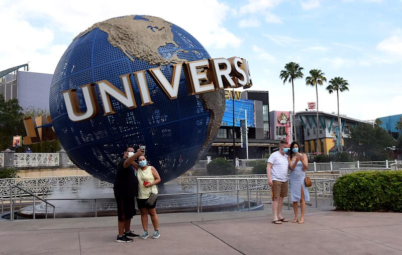 ORLANDO, UNITED STATES - MAY 14, 2020: Guests wearing face masks pose for selfies at the Universal Orlando's CityWalk as sections of the entertainment and retail district opened today for limited hours for the first time since Universal Orlando closed on March 15, 2020 due to the coronavirus pandemic. In addition to face coverings, temperature checks are also being required. Universal's theme parks will remain closed until at least May 31.- PHOTOGRAPH BY Paul Hennessy / Echoes Wire/ Barcroft Studios / Future Publishing (Photo credit should read Paul Hennessy / Echoes Wire/Barcroft Media via Getty Images)