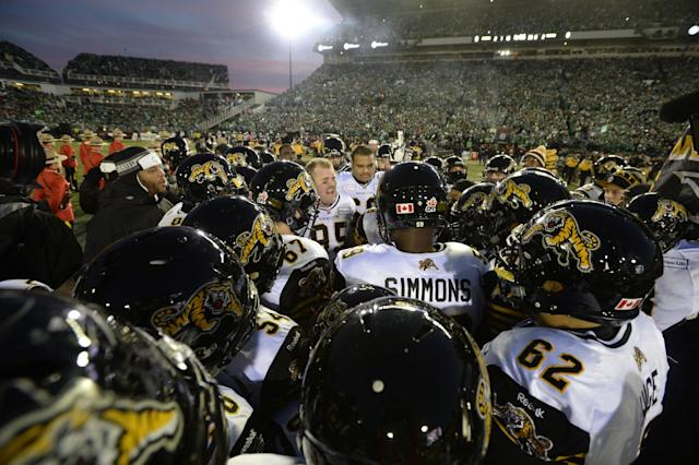 Members of the Hamilton Tiger-Cats take the field to face the Saskatchewan Roughriders in the Grey Cup, Sunday, Nov, 24, 2013, in Regina, Saskatchewan. (AP Photo/The Canadian Press, Frank Gunn)