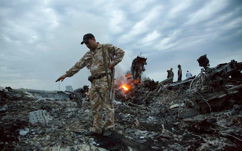In this July 17, 2014 file photo, people walk amongst the debris at the crash site of MH17 - AP