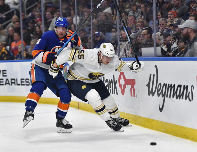 Buffalo Sabres defenseman Rasmus Ristolainen (55) and New York Islanders right wing Josh Bailey chase the puck along the boards during the first period of an NHL hockey game in Buffalo, N.Y., Saturday, Nov. 2, 2019. (AP Photo/Adrian Kraus)
