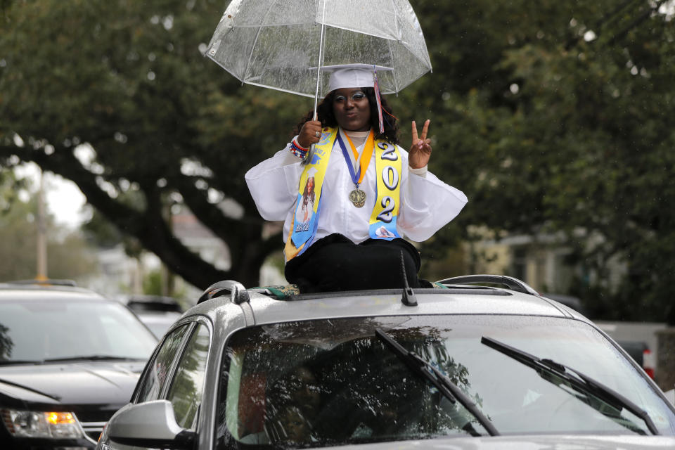 In New Orleans on May 27, 2020, graduates of New Orleans Charter Science and Math High School got out of their cars to receive diplomas one by one and then held a parade of cars through city streets. (AP Photo/Gerald Herbert)