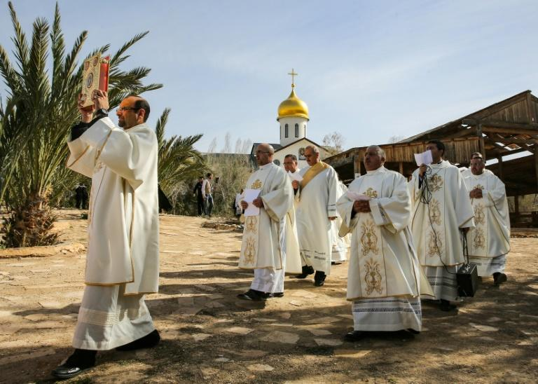 Roman Catholic clergymen walk in a religious procession at the site where Jesus is believed by Christians to have been baptised
