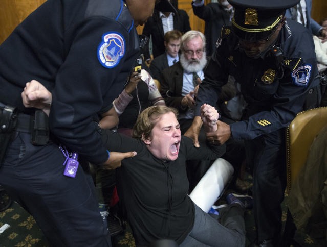 <p>U.S. Capitol Police officers remove a protester from the Senate Budget Committee hearing on Capitol Hill in Washington, Tuesday, Nov. 28, 2017. (Photo: Carolyn Kaster/AP) </p>