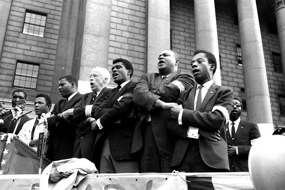 """Civil rights leaders clasp hands as they sing during the closing of memorial ceremonies in New York, Sept. 22, 1963, for four girls killed in the bombing of the Birmingham, Ala., Sixteenth Street Baptist Church.  From right, are: author James Baldwin; James Farmer, president of the Congress of Racial Equality; unidentified man; and veteran Socialist leader Norman Thomas.  At a rally on Foley Square, Farmer charged the U.S. Department of Justice and President Kennedy with a share of the blame in the Sept. 15, bombing, and Thomas said he was """"ashamed that I was a white American,  when the bombing took place."""""""