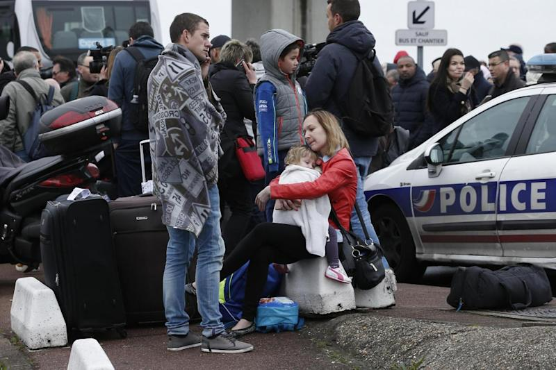 Evacuation: Travellers wait outside the airport (AP)