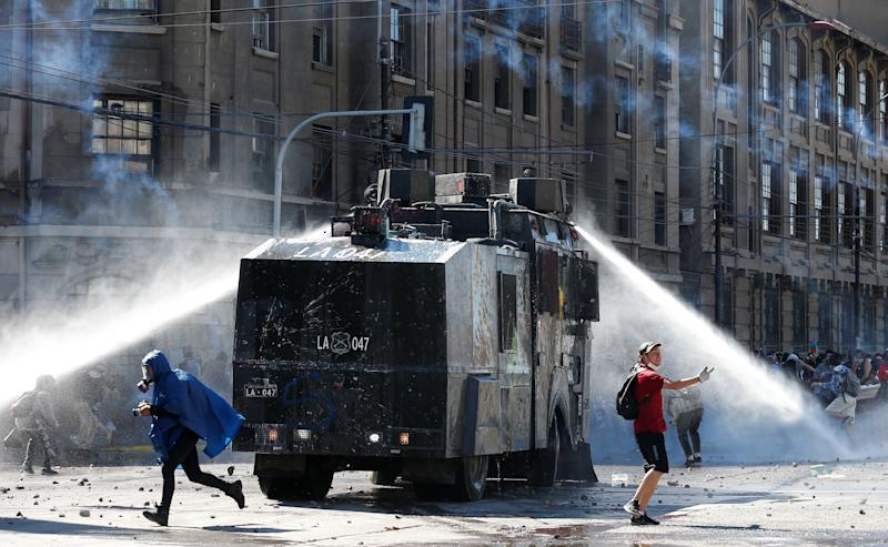 People walk away as riot police use a water cannon during a protest against Chile's government in Valparaiso, Chile on Oct. 28, 2019. (Photo: Rodrigo Garrido/Reuters)