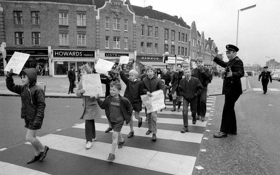 Industrial Disputes: Teachers Strike: All the schools in the Ealing area were closed for the day because of the teachers pay claim dispute. 7 year old Bily Fuller of Stanhope Junior School, Greenford, leads the demonstration down the Broadway with his sister Ann (12) OC Costain Senior Girls School, Greenford. December 1969 Z11596-006 (Photo by WATFORD/Mirrorpix/Mirrorpix via Getty Images)  - Getty