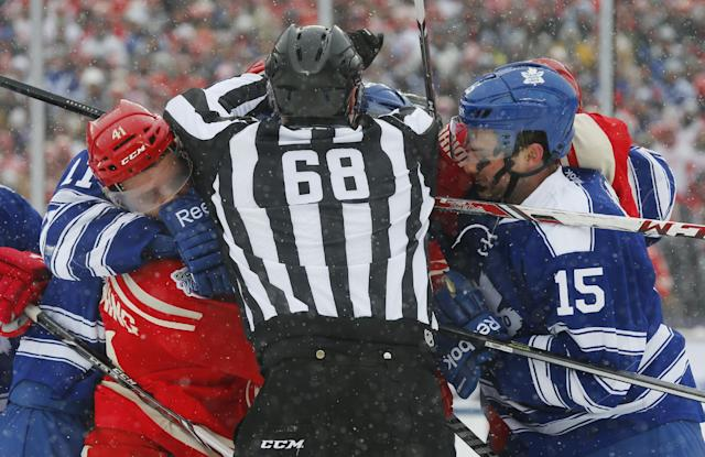 Linesman Scott Driscoll (68) separates Detroit Red Wings right wing Luke Glendening, left, and Toronto Maple Leafs defenseman Paul Ranger (15) during a scuffle in the second period of the Winter Classic outdoor NHL hockey game at Michigan Stadium in Ann Arbor, Mich., Wednesday, Jan. 1, 2014. (AP Photo/Paul Sancya)