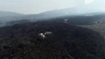 Aerial view of houses surrounded by lava from the Cumbre Vieja volcano, on the island of La Palma