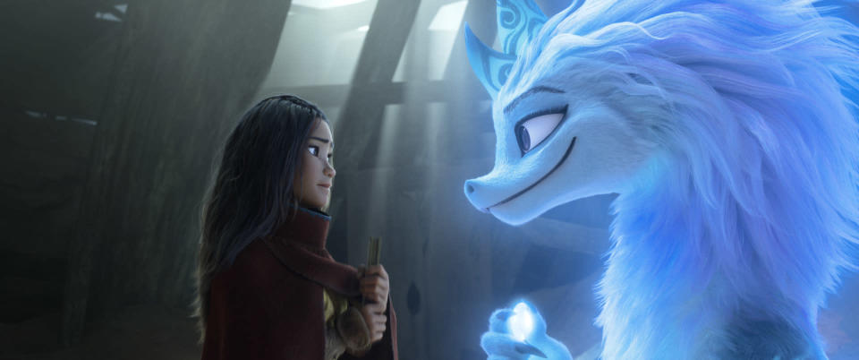 """Animated character Raya, voiced by Kelly Marie Tran, left, appears with Sisu the dragon in a scene from """"Raya and the Last Dragon."""" (Disney+ via AP)"""