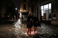 Tourists waded in thigh-high galoshes or barefoot through the submerged alleys