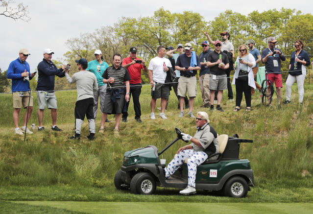 FILE - In this May 17, 2019 file photo, John Daly drives his cart off the 16th tee during the second round of the PGA Championship golf tournament, at Bethpage Black in Farmingdale, N.Y. Organizers of the British Open have refused a request by former champion John Daly to use a golf cart at the championship in Royal Portrush this month. Daly had applied to use a cart because of his arthritic right knee. The R&A said it was declining the request because walking the course is an integral part of the championship and is central to the tradition of links golf. It said it was important to ensure that, as far as possible, the challenge is the same for all players in the field. (AP Photo/Andres Kudacki, FIle)