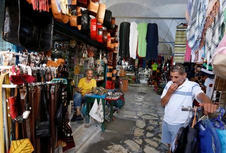Shopkeepers wait for customers in front of a souvenir shop following Thomas Cook's collapse, in Hammamet