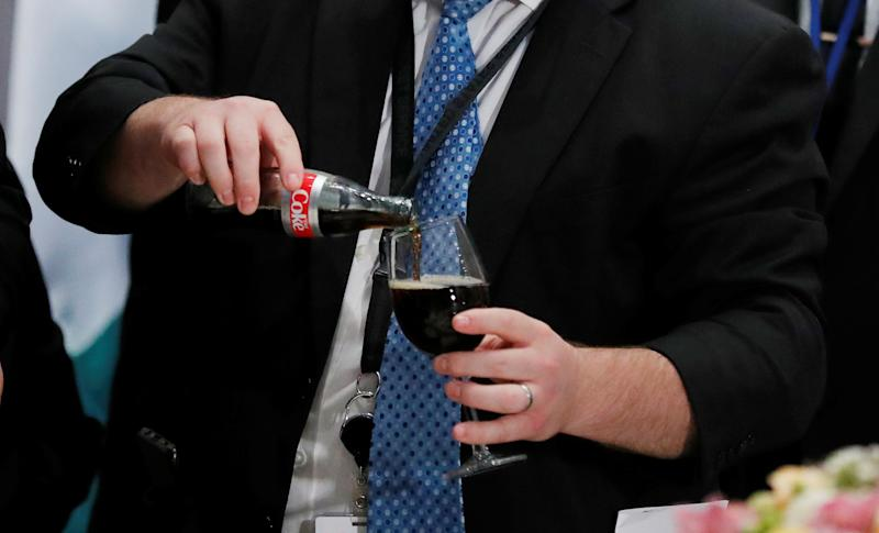 A White House staff member from the presidential food service pours a Diet Coke for U.S. President Donald Trump before the start of a luncheon for world leaders at the United Nations during the 73rd session of the United Nations General Assembly in New York, U.S., September 25, 2018. REUTERS/Carlos Barria