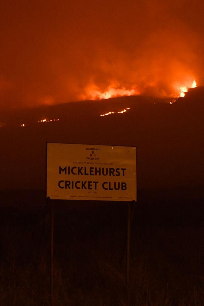 A view of the sign to Micklehurst Cricket Club below burning moorland (Picture: Getty)