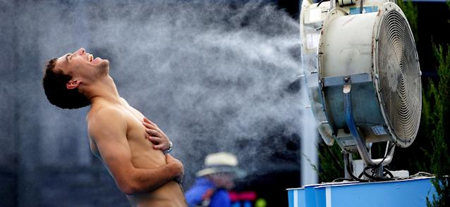 In this photo released by Tennis Australia, Poland's Jerry Janowicz is sprayed with cool water at the Australian Open tennis championship in Melbourne, Australia, Thursday, Jan. 16, 2014. The Australian Open organizers implemented the Extreme Heat Policy when the temperature topped 43 C (109 F) and play was halted for just over fours on the outside courts but continued on the covered show courts. (AP Photo/Tennis Australia,Fiona Hamilton)