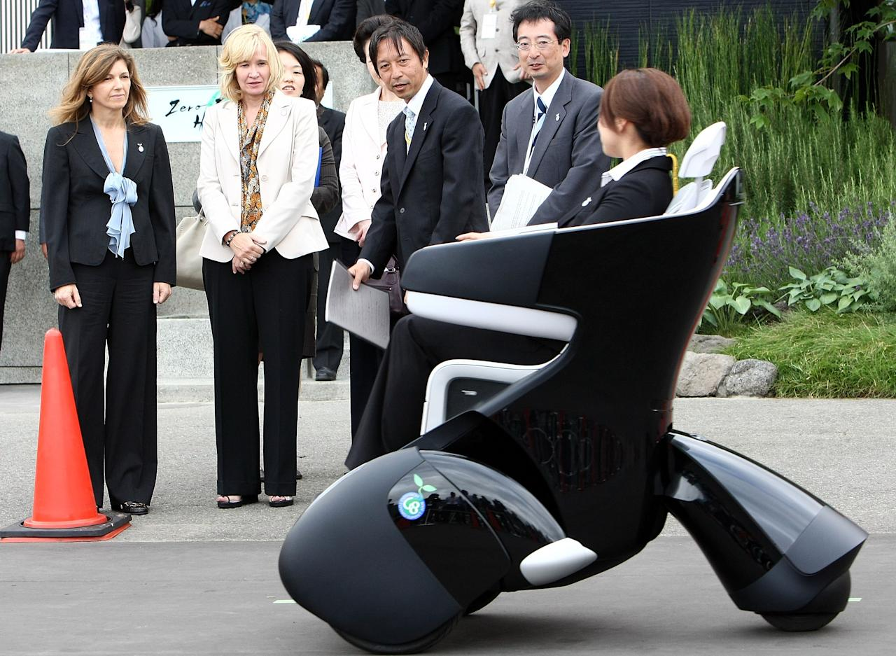 RUSUTSU, JAPAN - JULY 08:  Margarida Sousa Uva (L), wife of European Commission President Jose Manuel Barroso and Laureen Harper (2L), wife of Canadian Prime Minister Stephen Harper watch the demonstration of Toyota Motor Corporation's Personal Mobility i-REAL during a concept car trial ride event upon their visit to the International Media Center at Rusutsu Resort on July 8, 2008 in Rusutsu, Hokkaido, Japan. During this 3-day Summit meeting, leaders from the eight strong industrial countries discuss on issues such as world economy, environment and climate changes and development in Africa.  (Photo by Junko Kimura/Getty Images)
