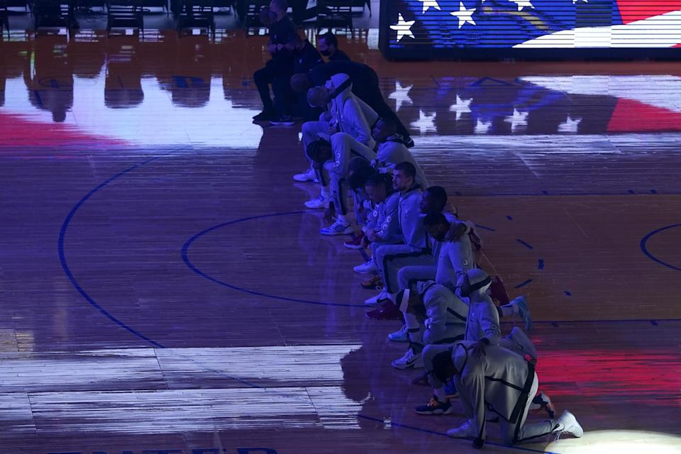 Clippers players and coaches kneel on court.