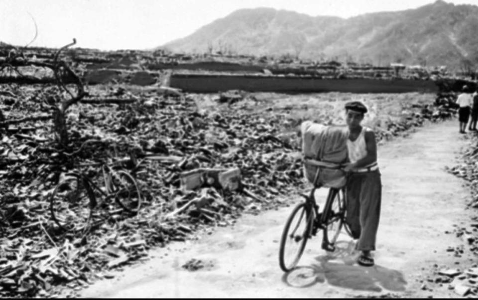 FILE - In this September 1945, file photo, a Japanese man pushes his loaded bicycle down a path that had been cleared of rubble after the atomic bombing of Nagasaki, Japan, on Aug. 9, 1945. The city of Nagasaki in southern Japan marks the 75th anniversary of the U.S. atomic bombing of Aug. 9, 1945. It was a second nuclear bomb dropped by the U.S. three days after it made the world's first atomic attack on Hiroshima. Japan surrendered on Aug. 15, ending World War II and its nearly a half-century aggression toward Asian neighbors. Dwindling survivors, whose average age exceeds 83, increasingly worry how they can pass on their lessons to younger generations and achieve nuclear weapons elimination.(AP Photo, File)