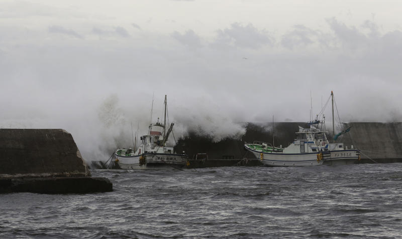 Big waves go over breakwater near anchored fishing boats in Fujisawa, near Tokyo, Monday, Sept. 16, 2013. Powerful typhoon Man-yi was bearing down on Japan and went past Tokyo on Monday, leaving one dead and dumping torrential rains, damaging homes and flooding parts of the country's popular tourist destination of Kyoto, where hundreds of thousands of people were ordered to evacuate to shelters. (AP Photo/Shizuo Kambayashi)