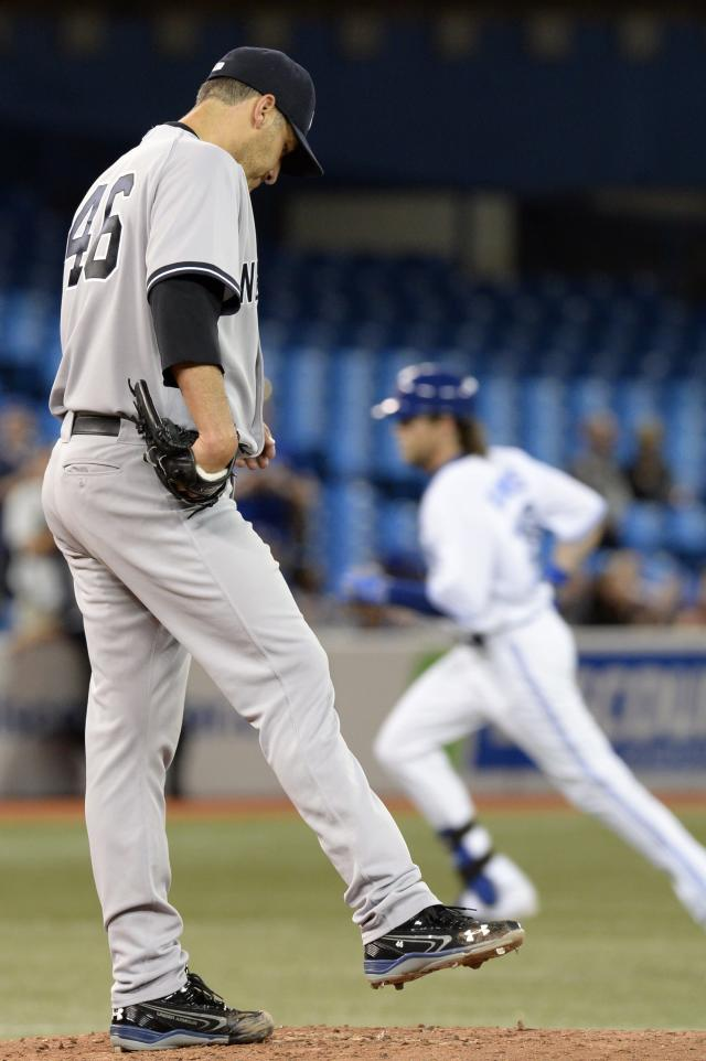 New York Yankees starter Andy Pettitte reacts as Toronto Blue Jays' Colby Rasmus rounds the bases after his solo home run during fourth inning MLB American League baseball action in Toronto, Tuesday, Sept.17, 2013. (AP Photo/The Canadian Press, Frank Gunn)