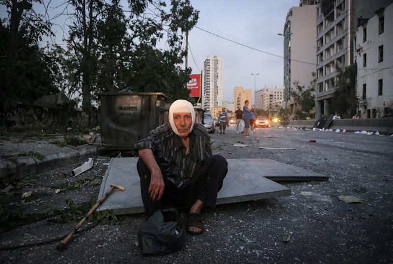 04 August 2020, Lebanon, Beirut: An elderly Lebanese man sits with a bandage on his head near the site of a massive explosion that rocked Beirut's port. Photo: Marwan Naamani/dpa (Photo by Marwan Naamani/picture alliance via Getty Images)