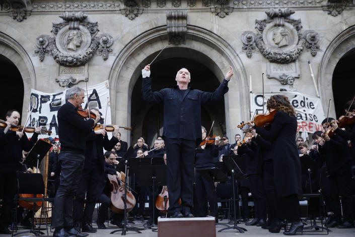 Michel Dietlin prepares to conduct striking musicians of the orchestra outside the Palais Garnier opera house Saturday, Jan. 18, 2020 in Paris. As some strikers return to work, with notable improvements for train services that have been severely disrupted for weeks, more radical protesters are trying to keep the movement going. (AP Photo/Kamil Zihnioglu)