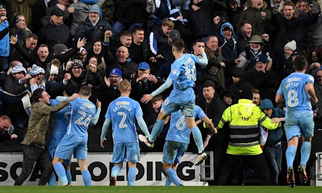 Coventry City players and fans celebrate Maxime Biamou's winner against MK Dons.