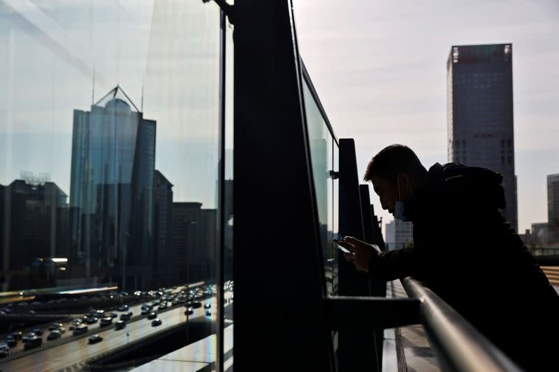 A man looks at his mobile phone while standing on a balcony overlooking the central business district in Beijing