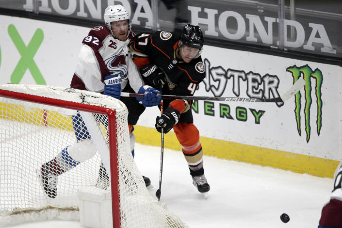 Anaheim Ducks defenseman Hampus Lindholm, right, passes the puck away from Colorado Avalanche left wing Gabriel Landeskog during the second period of an NHL hockey game in Anaheim, Calif., Sunday, Jan. 24, 2021. (AP Photo/Alex Gallardo)