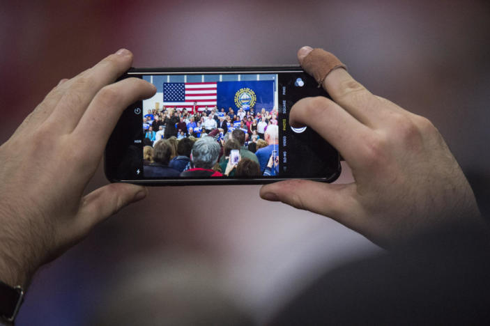 <p>A man photographs Democratic presidential candidate Hillary Clinton speaking to supporters during a Manchester GOTV organizing event with Gabby Giffords and Mark Kelly at Henry J. McLaughlin Middle School in Manchester, on Wednesday, Feb. 3, 2016.<i> (Photo: Jabin Botsford/The Washington Post via Getty Images)</i></p>