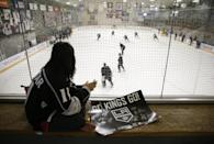 Melissa Hom, of Manhattan Beach, Calif., watches the Los Angeles Kings players skate during the team's NHL hockey practice Friday, Sept. 19, 2014, in El Segundo, Calif. The Kings went through their first workouts of training camp Friday as they prepare for their run at a third NHL title in four seasons. (AP Photo/Jae C. Hong)