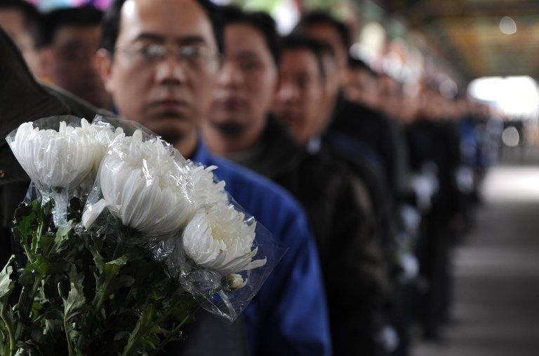 """Villagers queue to pay their respects to retired local Communist Party chief Wu Renbao at his home in Huaxi village on March 19, 2013. Residents of China's """"richest village"""" bid farewell to the man who made Huaxi a socialist paradise, with a 20-vehicle funeral procession transporting his coffin and a helicopter flying overhead"""
