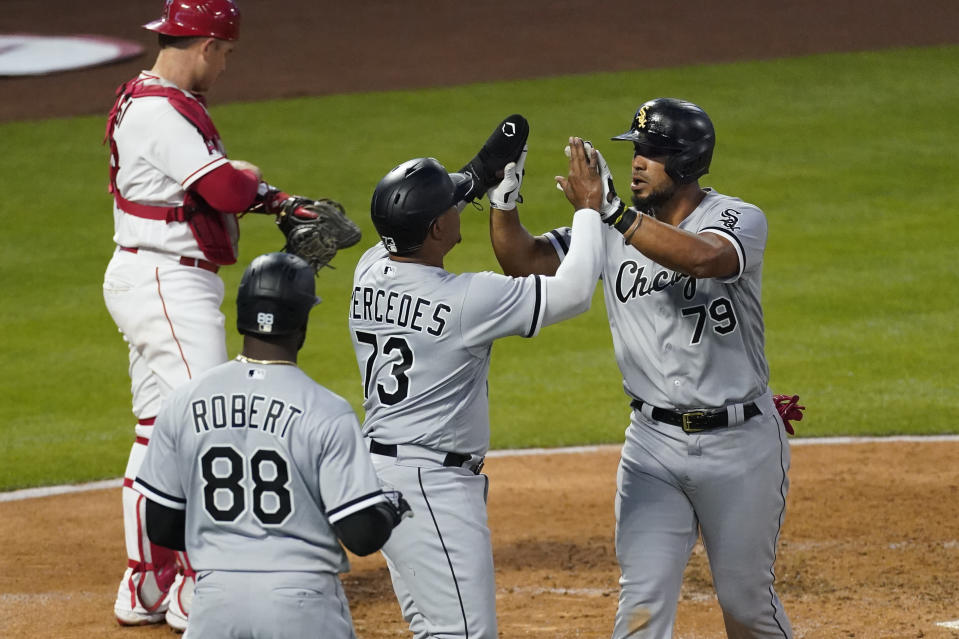 Chicago White Sox's Jose Abreu (79) high-fives Yermin Mercedes (73) after hitting a grand slam during the third inning of an MLB baseball game against the Los Angeles Angels Friday, April 2, 2021, in Anaheim, Calif. Mercedes, Tim Anderson, and Luis Robert (88) also scored. (AP Photo/Ashley Landis)
