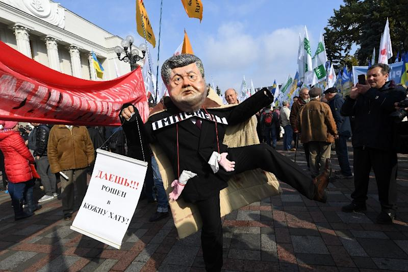 An activist wears a mask portraying Ukrainian President Petro Poroshenko who protesters say is not doing enough to combat corruption. (AFP Photo/Sergei SUPINSKY)