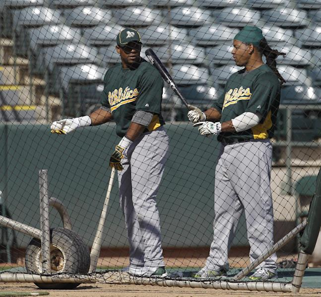 Oakland Athletics' Yoenis Cespedes, left, talks with Manny Ramirez before hitting during a baseball spring training workout Sunday, March 4, 2012, in Phoenix. (AP Photo/Darron Cummings)