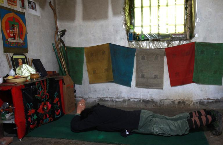 Gao Ming, a hermit in the Zhongnan mountains, worships before a shrine to her gods in her cottage in north China's Shaanxi province, on October 31, 2014