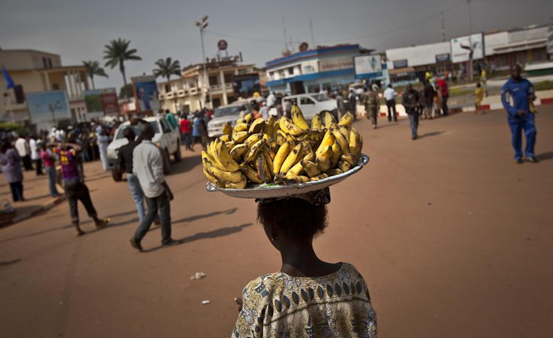 A young street vendor selling bananas walks over to take a look at a demonstration held by several hundred merchants calling for peace as negotiators prepare for talks with rebels from the north, in downtown Bangui, Central African Republic, Saturday, Jan. 5, 2013. The U.N. Security Council urged rebels in the Central African Republic on Friday to halt their military offensive, withdraw from cities they have seized, and take part in negotiations to find a political solution to the impoverished country's longstanding problems. (AP Photo/Ben Curtis)