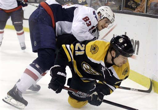 Washington Capitals center Jay Beagle (83) checks Boston Bruins defenseman Andrew Ference (21) as they compete along the boards for the puck during the first period of Game 7 of an NHL hockey Stanley Cup first-round playoff series, in Boston on Wednesday, April 25, 2012. (AP Photo/Elise Amendola)