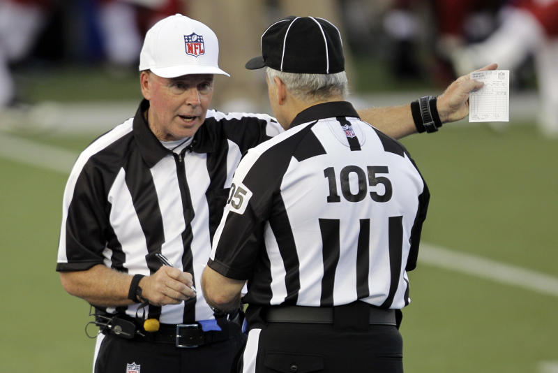 Referee Craig Ochoa, left, talks with field judge Rusty Spindel (105) during the first quarter of the NFL Hall of Fame exhibition football game between the Arizona Cardinals and New Orleans Saints, Sunday, Aug. 5, 2012 in Canton, Ohio. (AP Photo/Gene J. Puskar)