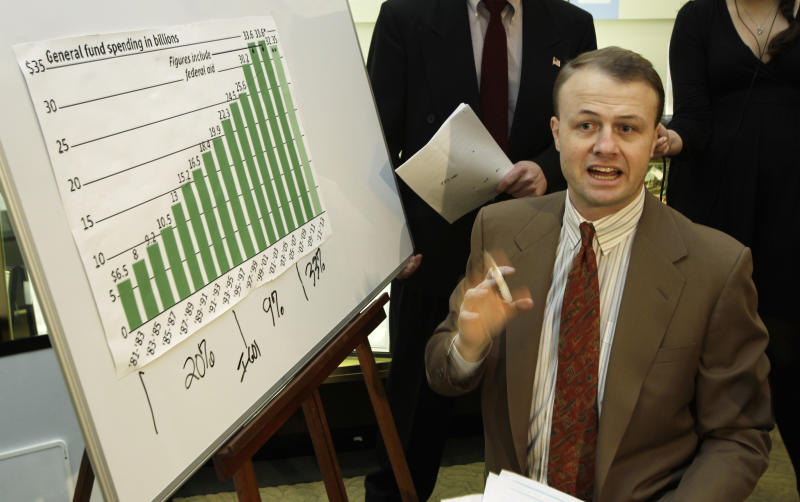 Initiative activist Tim Eyman, center, talks to reporters at the Capitol in Olympia, Wash., next to a chart of state government spending over the years, Monday, Jan. 10, 2011. Eyman filed an initiative Monday that requires a two-thirds supermajority for the Legislature to raise taxes. The Washington state legislature opens it's 2011 session on Monday. (AP Photo/Ted S. Warren)
