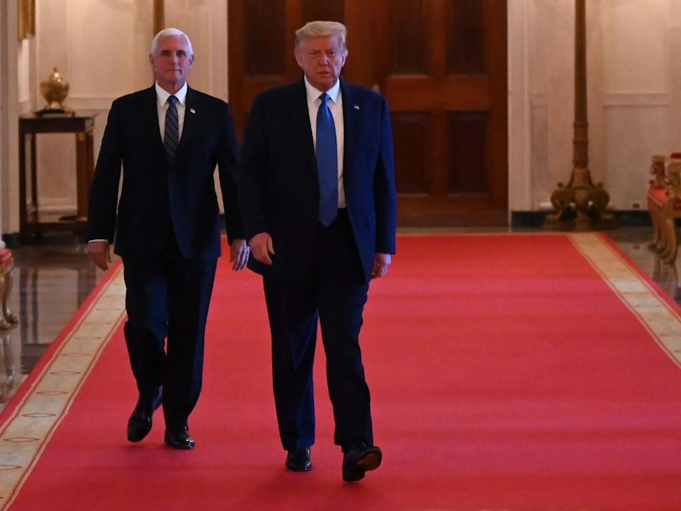 President Donald Trump and Vice-President Mike Pence arrive to participate in a roundtable with stakeholders positively impacted by law enforcement, in the East Room of the White House: AFP via Getty Images
