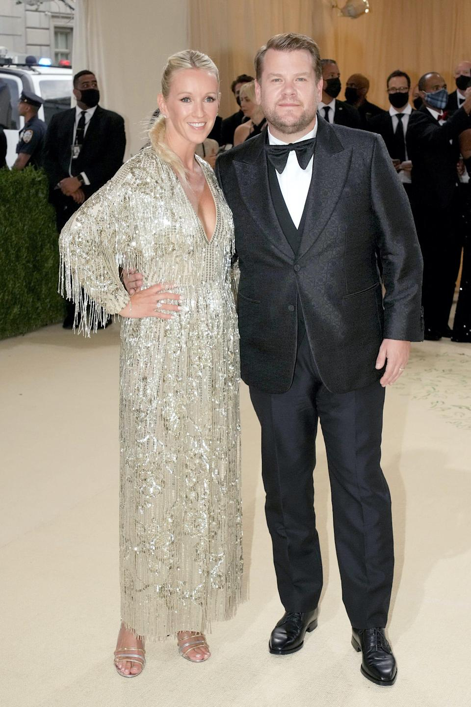 Julia Carey and James Corden stand on a red carpet.