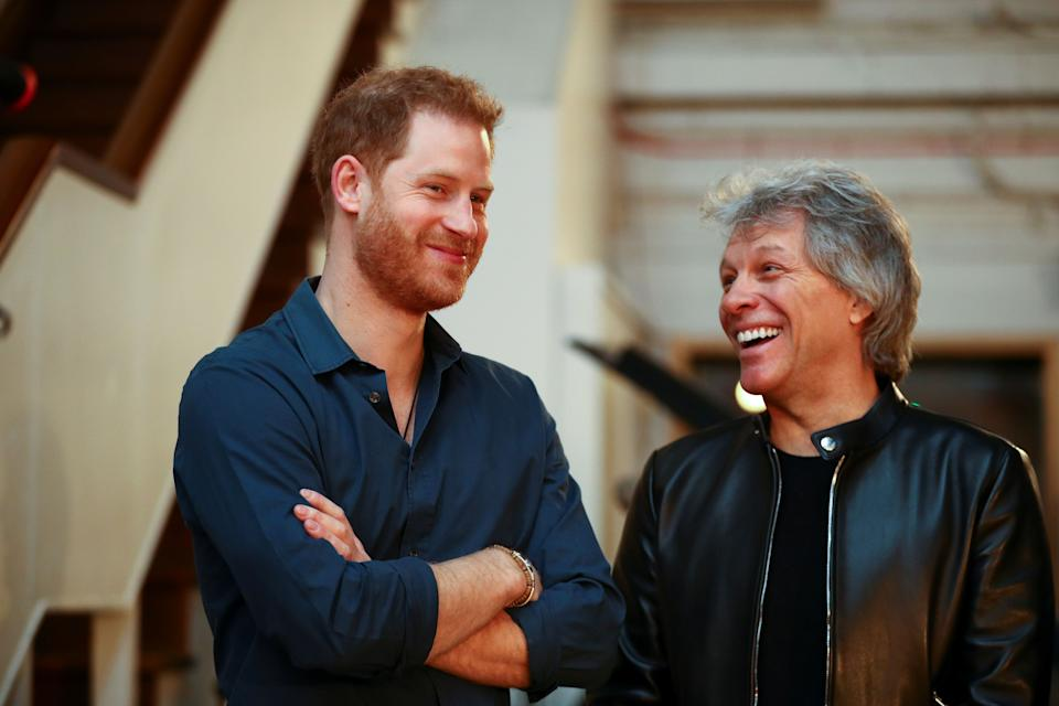 Britain's Prince Harry, Duke of Sussex (L) and US singer Jon Bon Jovi gesture at Abbey Road Studios in London on February 28, 2020, where they met with members of the Invictus Games Choir, who were there to record a special single in aid of the Invictus Games Foundation. (Photo by HANNAH MCKAY / POOL / AFP) (Photo by HANNAH MCKAY/POOL/AFP via Getty Images)