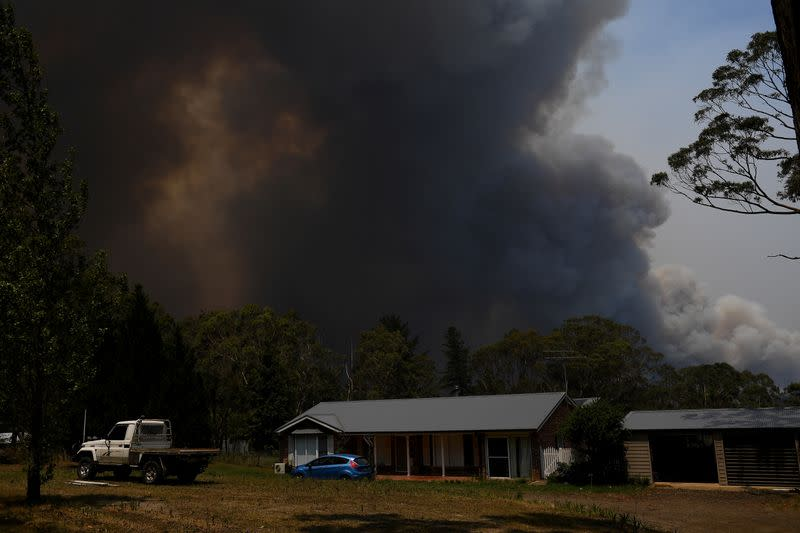 FILE PHOTO:  A home is seen as smoke from the Grose Valley Fire rises in the distance, at Bilpin, New South Wales