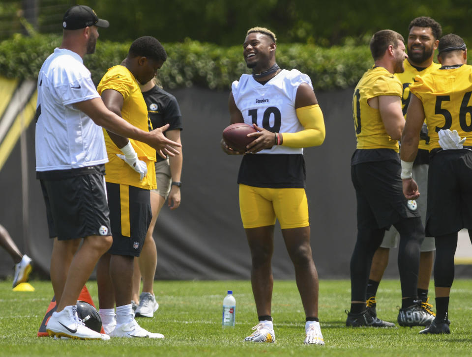 Pittsburgh Steelers wide receiver Juju Smith-Schuster (19) jokes with quarterback Ben Roethlisberger, left, during the NFL football team's training camp in Pittsburgh on Friday, July 23, 2021. (Steve Mellon/Pittsburgh Post-Gazette via AP)