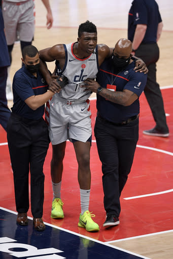Washington Wizards center Thomas Bryant (13) is helped off the court after he was injured during the first half of an NBA basketball game against the Miami Heat, Saturday, Jan. 9, 2021, in Washington. (AP Photo/Nick Wass)