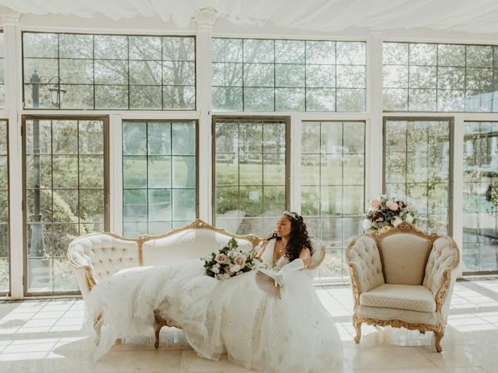 A bride sits on a couch in front of a wall of windows.